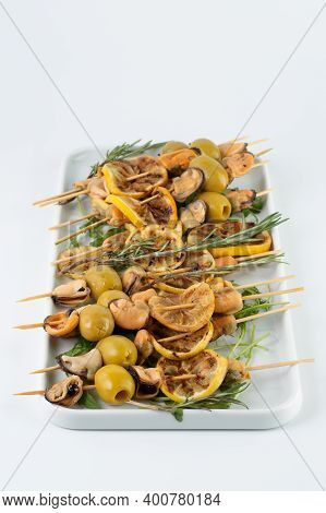 Kebab With Mussels, Lemons And Olives, Garnished With Rosemary On A White Plate. Kebab For A Buffet
