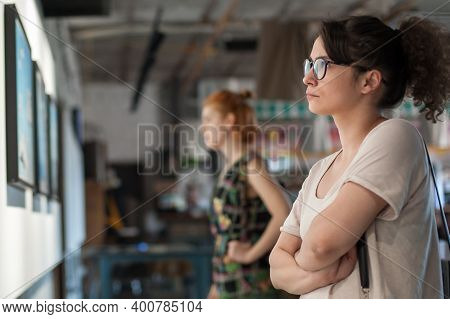 Two Girl Friends In Modern Art Exhibition Gallery Hall Contemplating Artwork. Abstract Painting