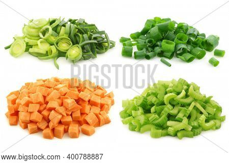 Cut leek, celery, spring onion and brunoise cut sweet potato pieces on a white background