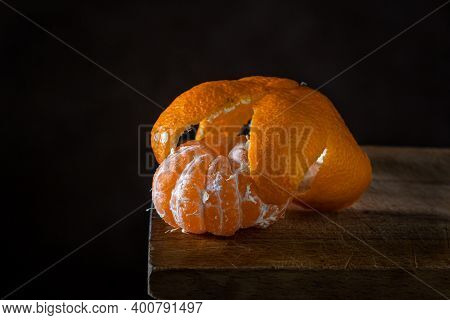 Peeled Tangerine On A Wooden Surface. Citrus Fruit. The Tangerine Peel Lies On The Peeled Tangerine