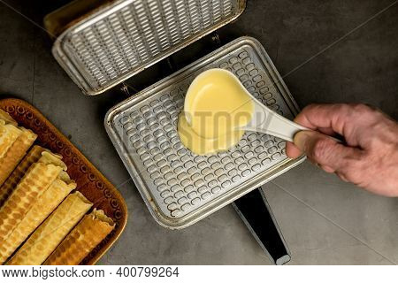 Cooking Waffles At Home - A Waffle Maker, Which Pours A Spoon Of Dough For Waffles. Ready-made Waffl