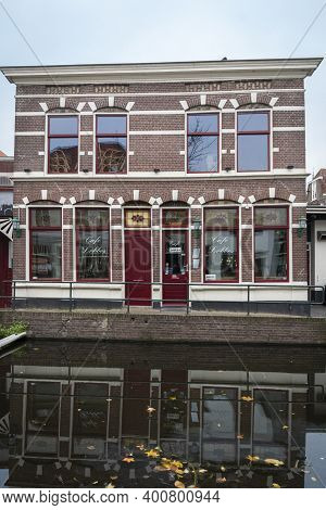 Gouda, Netherlands, November 2018 - Building Facade With A Canal In The Foreground In The City Of Go