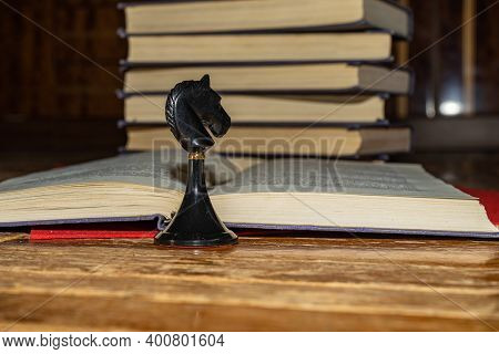 Knights Move. Chess Piece Black Knight On The Background Of An Open Book