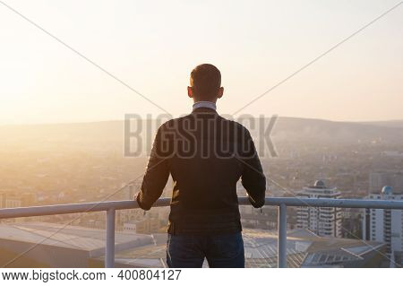 Muscular Man In Black Jacket Holds Hands On Grey Metal Handrails And Admires Sunrise Over Cityscape
