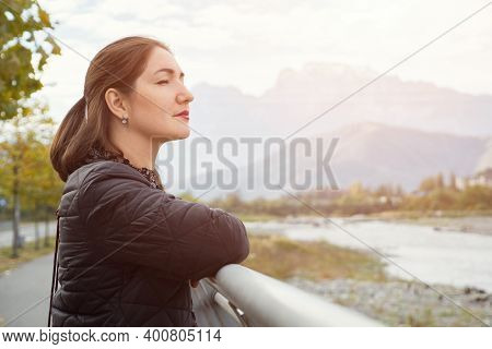 Young Woman With Long Loose Flowing Hair Stands Near Grey Metal Handrails And Looks At River Against