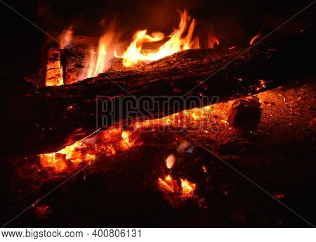 Old Wooden Beam Used As Firewood In A Bonfire With Embers.