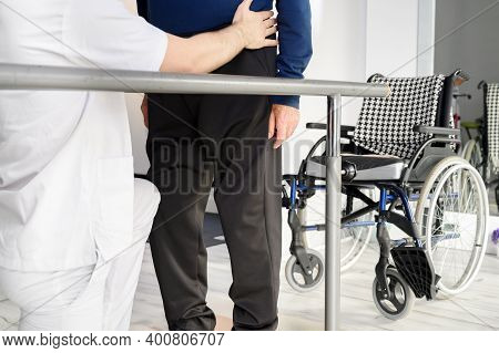 Senior Man Being Assisted By Physiotherapist In Rehab Center. High Quality Photo