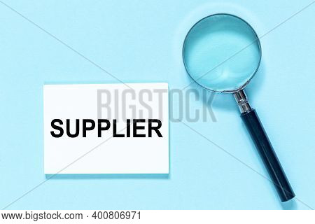 Supplier Word Made With White Card With Magnifier On Blue Background. Business And Industry Concept.