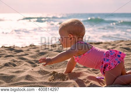 Kid Learns To Crawl. Child Is Crawling Along Sand. First Steps First Vacation