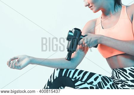 Athletic Young Female Massaging Hand By Handheld Massage Gun, Post-workout Recovery Routines, Close