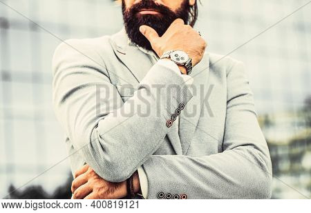 Portrait Successful Businessman In A Business Suit, Using The Watch On A City Background. Watch In A