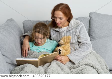 Mom Sitting On Couch With Her Daughter And Reading Book. Smiling Loving Mother Hugging Her Daughter