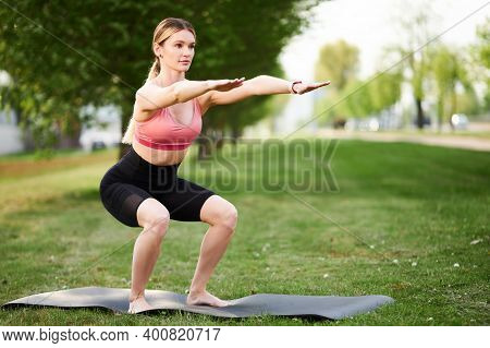Squats. Sports Woman In Fitness Clothes Squatting. Burn In Buttocks. Side View Of Young Woman In Spo