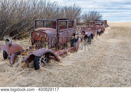 A Row Of Abandoned Vintage Cars On The Prairies In Saskatchewan