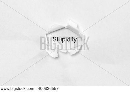 Word Stupidity On White Isolated Background, The Inscription Through The Wound Hole In Paper. Concep