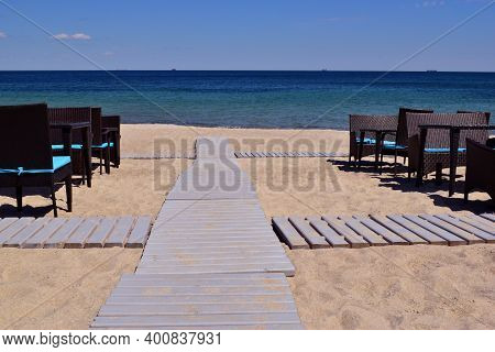 Tables And A Wooden Walkway To The Sea. A Wooden Walkway Leading From The Beach To The Sea With A Br