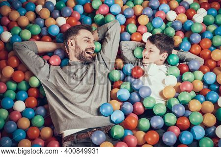 Dad And Son Look At Each Other While Lying.