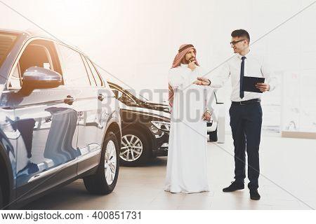 Arabic Man At Car Dealership. Salesman And Man Are Looking At New Cars.
