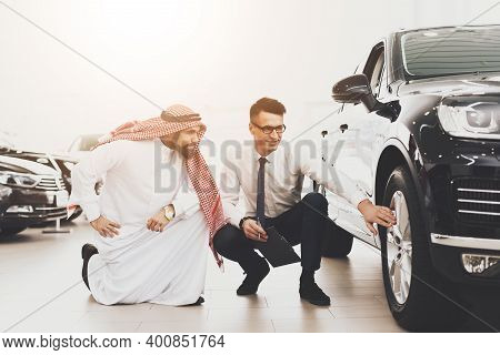 Arabic Man At Car Dealership. Salesman Is Showing Wheel On New Black Car.