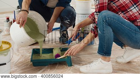 Close Up Of Caucasian Happy Nice Married Couple Man And Woman Pouring Paint And Preparing For Painti