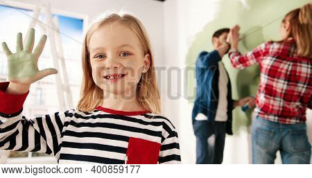 Close Up Portrait Of Joyful Little Cute Girl Smiling To Camera Showing Hand Palm In Green Paint. Mom