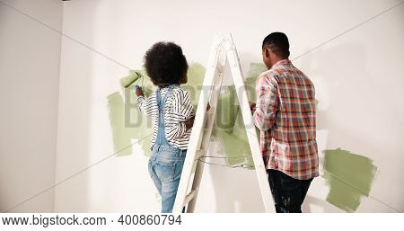 Back View Of African American Couple Male And Female Redesigning And Renovating Room In Own Apartmen