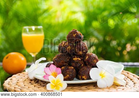 Sweet Dried Fruit Balls Decorated With Tropical Frangipani Flowers In Thailand On Koh Samui Island,