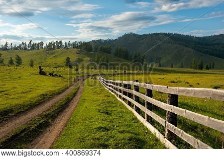 Russia. South Of Western Siberia, Mountain Altai. Green Pastures In The Mountain Valleys Fenced In B