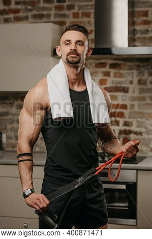 A Muscular Man With A White Towel On The Shoulders Is Posing With Pull Elastic Rope In His Apartment