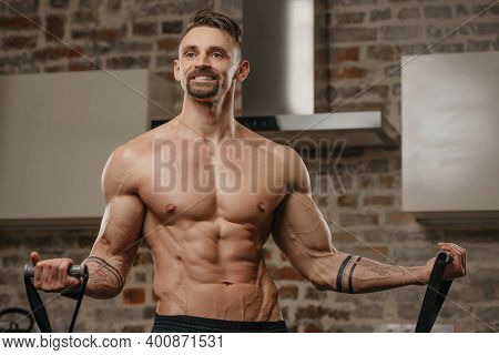A Muscular Man Is Working Out With An Elastic Pull Rope In His Apartment. Athletic Guy With Tattoos