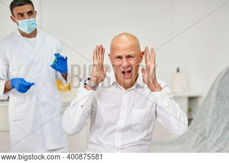 Antivirus Vaccination Concept .angry Furious Man Crying At Medical Clinic