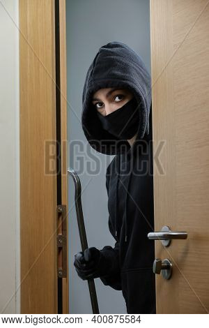 Thief Broke Into The Apartment. House Robbery By Woman In A Black Jacket And Black Mask And Crowbar.