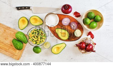 Avocado Halves, Pieces, Limes And Onions, Cup With Salt - Basic Guacamole Ingredients And Chef Knife