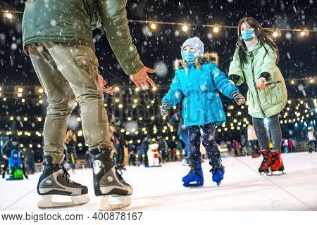 Skating Rink. Family Wearing The Medical Face Masks On The Ice Rink. Prevention Of Coronavirus And O