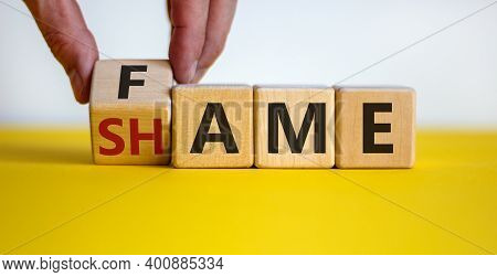 Fame Or Shame Symbol. Male Hand Flips Wooden Cubes And Changes The Word 'shame' To 'fame' Or Vice Ve
