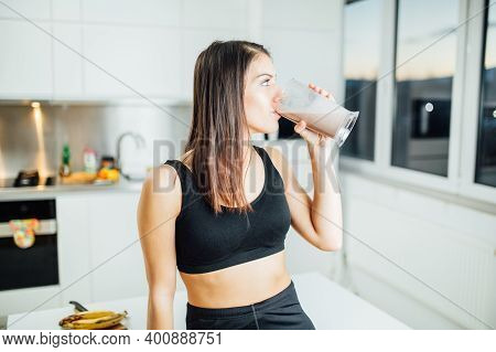 Woman In Sportswear Drinking Sweet Banana Chocolate Protein Powder Milkshake Smoothie. Drinking Prot