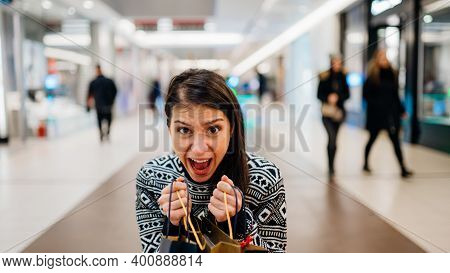 Excited Female Shopper Holding Bought Items In Colourful Bags. Customer In A Shopping Mall, Discount