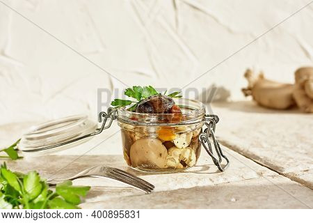 Marinated Mushrooms In Glass Jar, Herbs And On White Background. Canned Vegetatian Dish. Natural Lig