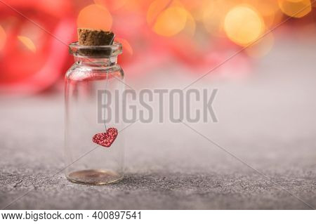 Glass Jar And Red Heart On Red Background. Concept Of Love In Valentine's Day.valentines Day Postcar