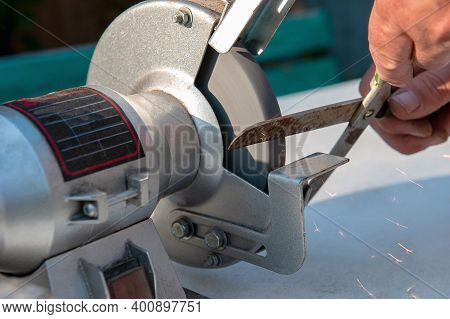 Close-up Of Mens Hands Sharpening Scissors On An Electric Sharpener. Repair Of Home Tools With Your