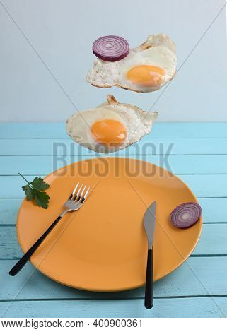 Two Flying Levitated Fried Eggs On Blue Backgrounds.