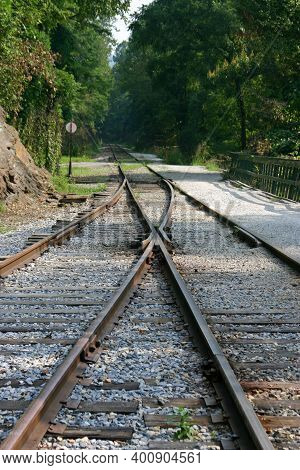 Old Style Railroad Train Tracks And Round Sign Where The Tracks Merge Together Or Go Their Separate