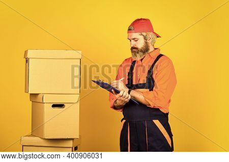 Foreman Planning. Unpacking Moving Boxes. New House At Moving Day. Bearded Man Builder In Boilersuit