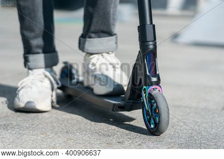 Young Teenager In Sneaker On Modern Extreme Stunt Kick Scooter In Skatepark