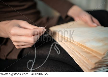Close Up Of Female Hands Binding Book At Home Or Diy Make Book With Old Paper