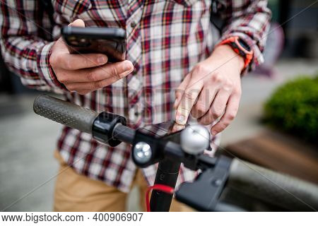Male Hands Modern Electric Scooter Turns On And Tunes. Caucasian Man Dressed Stylishly Casual Uses C