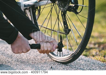 Close-up Of A Man Pumping Bicycle Wheel On The Street. Man Inflates Bicycle Wheel Using A Pump. Pump