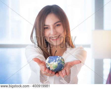 World Food Day Concept: Selective Focus Blue Earth Globe Of Apple, Asian Woman Giving Fruit. Element