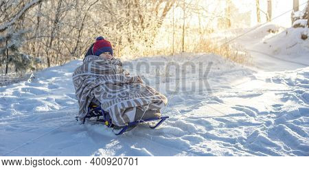 Mom Is Pulling A Child On A Sledge Walking On A Winter Sunny Day Out Of Doors. Baby Wrapped In A Bla