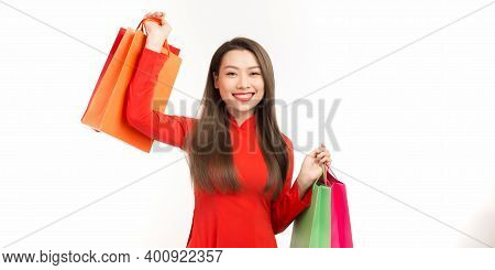Asian Woman In Traditional Vietnamese Dress, Ao Dai, Carrying Paper Shopping Bags As A Customer For